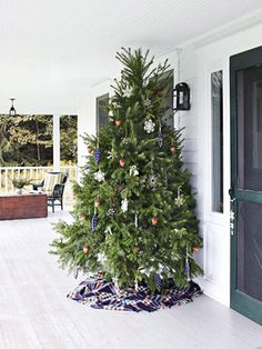 Christmas tree on the porch, I like the wool blanket as a tree skirt