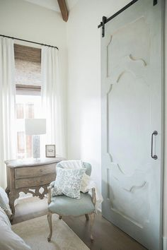 The barn door is a custom designed door from a local carpenter and painted by the designer in Annie Sloan - custom mix of Duck Egg Blue, Old White, French Linen, and Coco