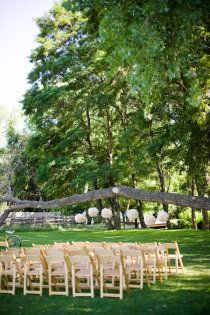 outside wedding.    Wooden folding chairs and tables with white clothes over burlap