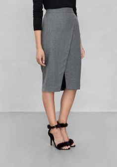 Made from a soft wool blend, this knee-length skirt with overlapping front features two front pockets.