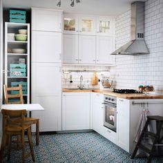 Cucina bianca con piano di lavoro in rovere, forno e cappa in acciaio inossidabile.