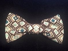 Adorable blue, white, and brown funky squares bow-tie. They are mounted on to a ribbon with elastic attached to the end to allow for stretching.
