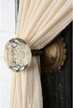 An antique door knob as a curtain tie back.