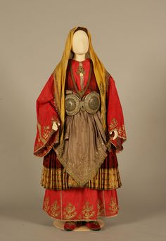 Bridal costume of Trikeri, Magnesia, Thessaly  Early 20th century    The costume of Trikeri has two fine white calico chemises and up to thirteen petticoats, the main ones being the kolovóli and the mallína. The 'good' outermost chemise is made of linen or silk, in white, blue, crimson, brown or green, and is adorned with gold or multicoloured embroidery. The dress is richly pleated, sleeveless and short, and the hem is often ornamented too.