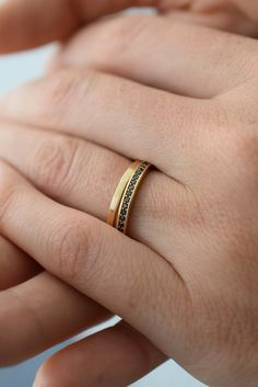 Crafted from 14K yellow gold, the handmade Pavé band is set with twenty-three delicate black diamonds. myeldesign.com