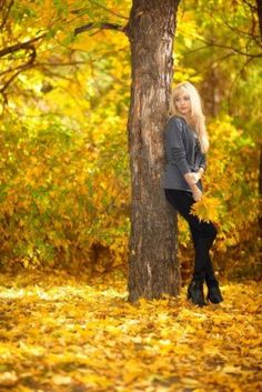 Autumn woman under tree in park with fall leaves