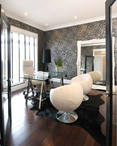 White & black modern office design with white & black wallpaper, Polished chrome glass-top sawhorse desk, white leather padded office chair, black cowhide rug, white pod chairs, white ornate baroque floor mirror and glossy black floor lamp.