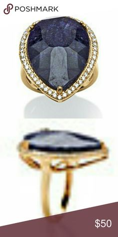 """SMOLDERING 18.25 CARATS BLUE SAPPHIRE RING SIZE 6 A smoldering 18.25 carats T.W. midnight blue sapphire cocktail ring. Surrounded by an elegant halo of cubic zirconia accents, .38 carat T.W. Set in 18k gold over sterling silver. Sizes 6 ITEM SPECIFICATIONS: RING METAL INFORMATION 18k Gold over Silver Finish Type:Bright Height:1/10"""" Length:1 1/64"""" Width:7/8"""" Shank Width:1/16"""" Style:Cocktail STONE INFORMATION Sapphire (Main/Largest Stone) Quantity:1 Size (mm):25x15 Cut:Pear…"""