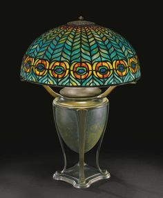 "TIFFANY STUDIOS ""PEACOCK"" TABLE LAMP, circa 1904 - with a ""Greek"" base shade impressed TIFFANY STUDIOS NEW YORK 1464-3 base impressed TIFFANY STUDIOS/NEW YORK/181 leaded glass and patinated bronze 20  3/4  in. (52.7 cm) high 15  7/8  in. (40.3 cm) diameter of shade circa 1904"