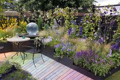 Rainbow walkway, vines, ornamental grasses, patio furniture, airy plantings, in purple, blues and yellow, with gazing ball, for exciting gar...