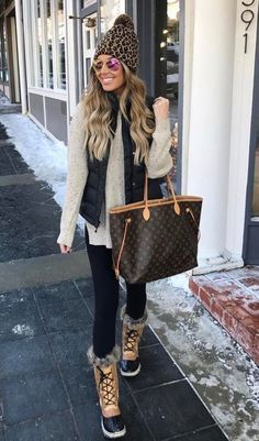 This is a cozy outfit for chilly days. Love the pompom hat and the bag. Also loving the ski vest and the snow boots. #casual #snow #winter #comfy #winterlayers #coldweatheroutfit, #cozyoutfit