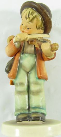 "Lot 307 in the 11.19.13 online & live auction! Darling vintage porcelain retired ""Little Fiddler"" German Goebel Hummel figurine # 2/0. It features a young boy playing a fiddle musical instrument. Incised mark on the bottom reads ""2/0"". Stamped in blue is the TMK- 3 The Stylized Bee (1960-1972) mark. Incised on the rim of the base is ""M. I. Hummel"", The Sister Maria Innocentia Hummel Signature. #Décor #Home #Collectable #POGAuctions"