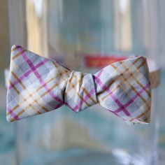 "The Purple and Gold Plaid Bow Tie is fun and festive for any occasion, it features magenta purple stripes with gold and light yellow stripe detailing atop a grey background. This bow tie is 100% Cotton. This bow tie also has a matching pocket square which is sold separately       The bow portion measures approximately 5"" x 2.5"" (12.8 x 6.4 cm) and the adjustable strap can be adjusted between 14""-20"" (35.6 - 50.8 cm).  This is a Self-Tie Bow Tie.      I always try to describe my items in the…"