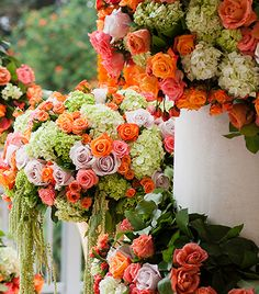 Hundreds of roses and hydrangeas in bright shades of pink, orange and green decorated the ceremony setting.