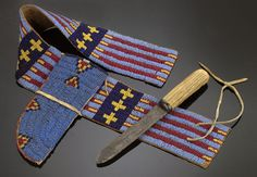 "Sioux Child's Knife, sheath, belt has sinew-sewn beadwork in colors of red, yellow, cobalt, and medium blue in a motif of narrow stripes separated by stacked crosses on the belt and small triangles on the sheath. Belt, ca 1870, closes with leather ties and a leather strip attaches sheath to belt. Knife has metal blade with much-used (loved) antler handle, belt 26.5"" long x 3"" wide; sheath 7.5"" high; knife 9.25"" high. Belt is probably a salvaged legging strip."