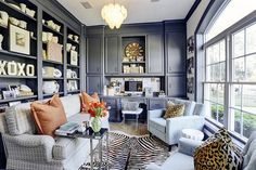 Gorgeous home office features wall to wall blue built-ins framing a built-in desk lined with an acrylic klismos chair alongside floor to ceiling blue bookcase filled with collectibles behind a geometric gray sofa with rolled arms layered with terracotta pillows and a nickel c side table. A pair of powder blue tufted club chairs stand across from the sofa accented with leopard print pillows on either side of a white garden stool.