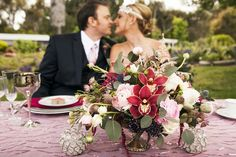 The sweethearts pose behind a Flower Duet wedding centerpiece designed with Pantone's 2015 Color of the Year, Marsala, as its main theme color. Eucalyptus leaves frame Cymbidiums, Ranunculus, Astilbe, Roses, Almond branches, Scabiosa blooms and Leucadendron. Flower Duet.  Photo by Jeannie Mutrais Photography.  #FinishWithFlowers