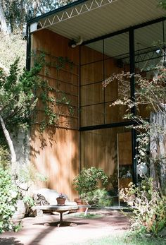 A shaded patio, with a corrugated steel overhang, and a wall of floor-to-ceiling windows connect the garden to the living room.  Eames house in Pacific Palisades.