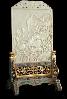 A Chinese imperial jade table screen and gilt cloisonne stand, the very light celadon coloured screen carved in relief with a crab amongst lotus and millet stems below a pierced stylized dragon top, Qianlong (1735-1795) The screen: 10 in. h. x 7 1/4 in. w. (25.5 x 18 cm) SOLD FOR $230,000 (March 2013)