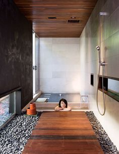 Japanese-style bathroom with small soaking tub and wood flooring