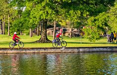 Lafreniere Park 3.  Two elderly women cycle along the lagoon on their way to badminton and a young couple strolls with their baby in the lovely early evening light at Lafreniere Park in Metairie LA.