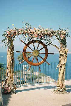 Beach Wedding Arch with a Ship Wheel and Pink Flowers | Brides.com