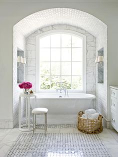 Designer Mark Williams makes the slipper tub the star of this luxurious bathroom by tucking it into a tile-covered arch beneath an oversized Palladian window. Larger 9 x 18 Carrara marble tiles surround the window while smaller marble subway tiles line the arch. To complete the traditional look, Mark chose Cararra marble and black granite basketweave tiles for the bathroom's floor.