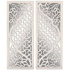 """Wood wall mirror with a floral cut-out design.      Product: 2 Pieces of wall décor   Construction Material: Wood and mirrored glass  Color: Silver and white    Dimensions: 48"""" H x 18"""" W each"""