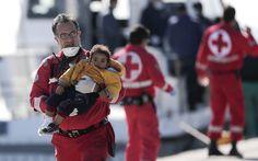 Voluntário da Cruz Vermelha carrega uma criança desembarcada de um navio de frete que levava cerca de 750 refugiados, a maioria síria, que tentavam chegar à Europa, em um porto de Creta, Grécia. O navio parou de funcionar a 70 milhas náuticas do porto (Foto: Petros Giannakouris/AP)