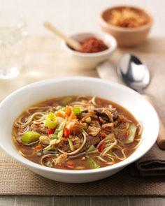 Pel de teentjes knoflook en hak ze fijn. Snijd het pepertje uit het bamipakket fijn. Verhit een wok, voeg 4 el olie toe en roerbak hierin de knoflook, het pepertje en de groenten ca. 1 min. Voeg de boemboe en de vleesreepjes aan de groenten toe en wok ca. 3 min. mee. Voeg 1½ l kokend water toe en breng aan de kook. Voeg de mie toe en laat in ca. 3 min. zachtjes gaar worden. Breng de soep op smaak met wat Conimex Ketjap Manis. Verdeel de groentesoep over 4 diepe borden of kommen en bestrooi…