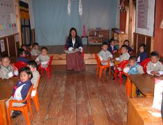 """The first AMI Montessori class in Bhutan.  This is the classroom """"before."""" Children stayed seated on plastic chairs at large tables and learned from posters on the wall, from workbooks, and from listening to the teacher. This is still the method of education in many places throughout the world.  """"after."""" Children are invited to choose a work, given a lesson, and can work for as long as they choose without interruption.  By Susan Stephenson."""