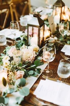 Nestled into the garland table runner, candlelit lanterns set the mood and create instant atmosphere for this barn wedding.Via Happy Wedd