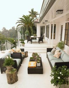 Gorgeous, chic city deck patio space. Black outdoor furniture, green blue outdoor cushions, outdoor coffee table, tree trunk accent table, French windows and outdoor dining set!