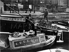 Manoeuvering narrow boats in the dock with barge poles on the Grand Union Canal, England.