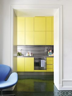 Yellow cabinets by Saari built to the ceiling provide ample storage in the Stockholm kitchen of Swedish set designer and art director Johan Svenson. The counters and backsplash are stainless steel.    - ELLEDecor.com