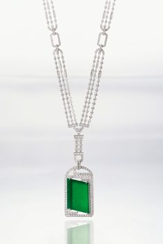Jadeite and diamond pendant long chain necklace. The jadeite plaque of highly translucent emerald green colour, surrounded by princess- and brilliant-cut diamonds, surmounted by a pendant loop set with baguette diamonds, accompanied by a necklace of Art-Deco design set with princess- and brilliant-cut diamonds, length approximately 700mm; and an interchangeable cord necklace decorated with brilliant-cut diamonds, mounted in 18 karat white gold