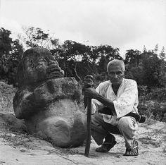 Un lugareño posa frente a una escultura olmeca conocida como La abuela