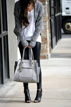 White blouse with grey stylish sweater and plan grey leather hand bag and black leather pant and black leather high heels shoes