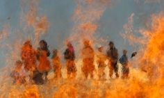 Afghan children watch burning expired medical items and food on the outskirts of Jalalabad, Afghanistan.