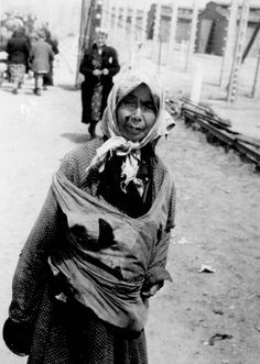 Birkenau, Poland, May 1944, A woman deemed unfit for work, in front of the entrance to the camp.