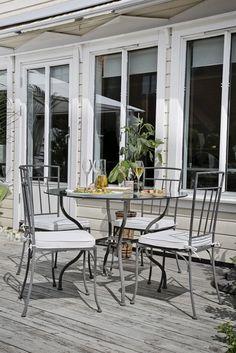 Terrassen ligger på bakkeplan med direkte utgang fra stuen. Hvite steiner, grønne planter og jernmøbler sender tankene mot varmere strøk. Tanks, Planters, Patio, Outdoor Decor, Home Decor, Beautiful, Decoration Home, Room Decor, Shelled