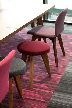 Shades of pink! In this office seating area we have used different styles and shades of pink seating, including a burgundy stool, a lilac chair and a fushia pink chair on a pink and grey carpet which are muted somewhat by the presence of a grey stool and the grey carpet surrounding it. The overall look is playful but still sophisticated.