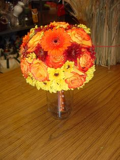 Orange and yellow wedding:  Fall bouquet of mixed orange and yellow flowers. Designed by WhimsicalWelcomes.com