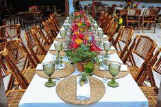 Decoração colorida em mesa comunitária. Cadeiras de madeira, sousplat de ratán, taças bico de jaca e mini abacaxi nos guardanpos dão um charme especial. Foto: Raphael Ranosi