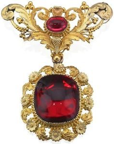 A 19th century garnet brooch, circa 1830 The large carbuncle garnet within a foliate tri-coloured gold surround suspended from a scrolling foliate surmount with central oval cabochon-cut garnet, closed back settings.