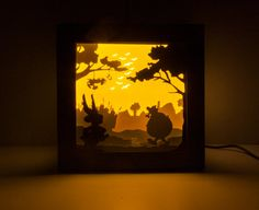 As Obelix says: Ils sont fous ces romains!  This is a very special handmade night light inspired by the famous comic Asterix, along with his best friend Obelix and their adorable dog, Idefix, several Romans shaking to the left and who is this guy tied hand and feet with a gag in his mouth, hanging on the tree? Of course is Cacofonix! Five colored papers, hand cut and layered to provide a 3D scene. Placed in a hand painted hard paper box and protected with plexiglass. Perfect for any room of…