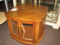 End table with storage featuring wired doors and veneer top $125. Available in-store
