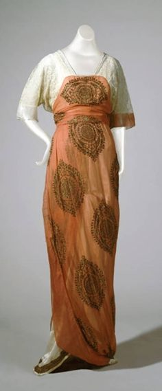 Poiret, Paul ((1879-1944) Paris, France): 1914, chiffon, silk underskirt and train, high-waisted bodice and overskirt embroidered with medallions, lace yoke and elbow-length sleeves, train banded with braid at bottom.