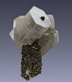 Calcite crystals on top of a quartz crystal covered-in by small pyrite crystal.