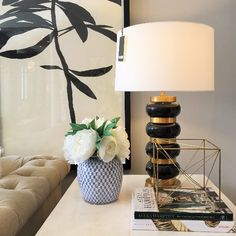 Alice Lane Home Collection   Black and brass lamp, blue and white jar with white peonies.
